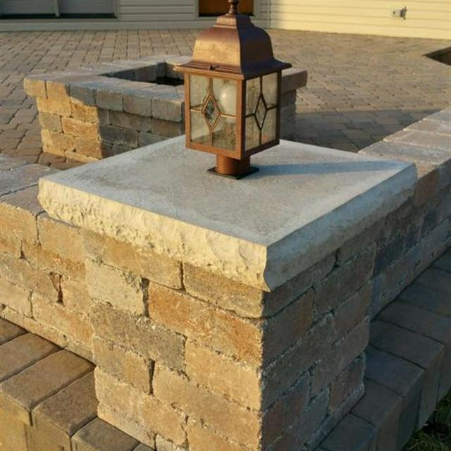 Close up view of square brick column in front of back of tan house
